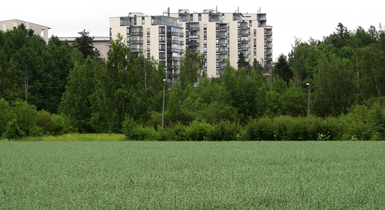 A photograph showing green area and some apartment buildings.